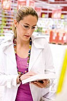 Woman looking at book in supermarket