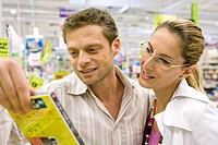 Couple looking at DVD together in store