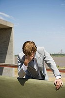Businessman leaning against wall holding head