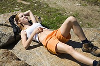 Young woman having rest after trekking in the mountains