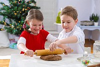 Two children rolling out dough for Christmas biscuits