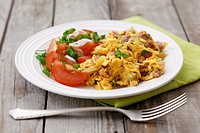 Scrambled egg with ham, parsley and tomato salad