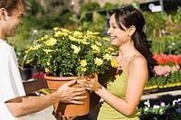 Young couple choosing potted flowers in garden centre