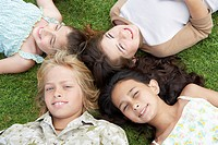 Smiling Pre_teen Children Lying on backs in circle on Grass overhead view