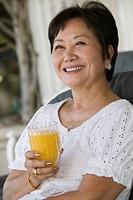 Woman drinking orange juice smiling outdoors