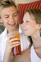 Young couple on sofa woman giving man iced drink close up