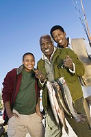 Male members of three generation family holding fishes smiling portrait