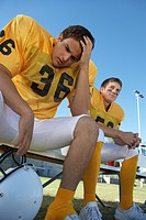 Two football players sitting on bench low angle view