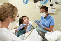 Two dentists examining female patient in surgery