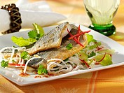 Sea bass fillets with rice noodles and salad leaves