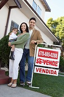 Family standing in front of house with For Sale sign portrait