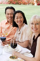 Three people smiling while sitting at outdoor table holding wine glasses