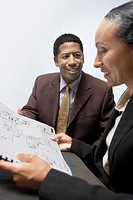 Businessman and Businesswoman Looking at Plans in Office