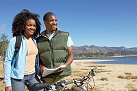 Young Couple on Mountain Bikes Using Map by lake