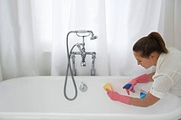 Young woman cleaning bathtub