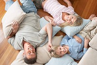 Father and Children Lying on pillows and cushions on wood Floor overhead view