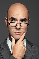 Bald man wearing glasses with hand on chin