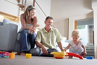 Happy parents watching toddler playing with toys on living room floor
