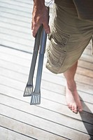 Man in shorts Holding Tongs on wooden porch low section high angle view