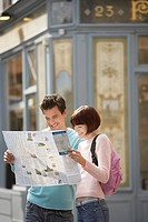 France Paris Couple reading map on street corner