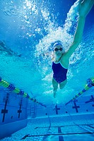 Female swimmer racing underwater in pool