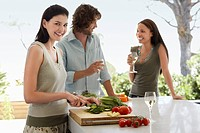 Friends talking drinking wine preparing food at a dinner party outside