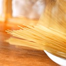Uncooked spaghetti falling into a deep plate