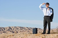 Businessman in sunglasses with briefcase in desert, looking into distance