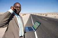 African man with laptop on deserted highway
