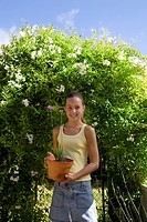 Girl 10_12 with flower pot by hedge, smiling, portrait