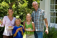 Family of four having barbeque, smiling, portrait