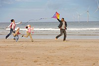 Family running on beach with kite