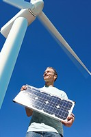 Man holding solar panel under windmill (thumbnail)