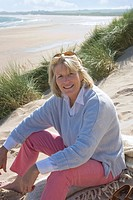 Portrait of mature woman sitting on beach