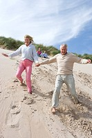 Senior couple running down on beach (thumbnail)
