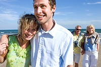 Young couple walking on beach, senior couple in background