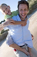 Portrait of father piggybacking son on beach
