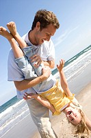 Father holding daughter upside down on beach (thumbnail)