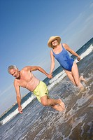 Senior couple walking in sea (thumbnail)