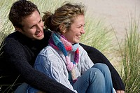Young couple sitting on beach (thumbnail)