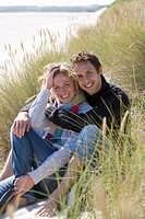 Portrait of young couple sitting on beach