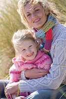 Portrait of mother sitting with daughter on beach