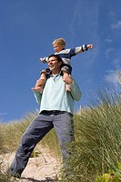 Father carrying son on shoulders at beach, low angle view