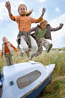 Young children jumping over boat