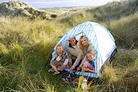 Young family sitting in tent camping