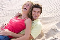 Young couple relaxing in sand laughing