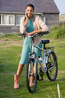 Portrait of young mixed race woman with bicycle outdoors