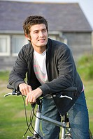 Portrait of young man on bicycle outdoors