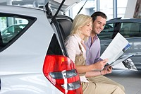 Couple looking at new car brochure