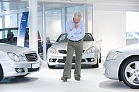 Man looking at car in showroom